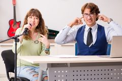 The young woman during music lesson with male teacher. Young women during music lesson with male teacher royalty free stock photos