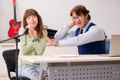 The young woman during music lesson with male teacher. Young women during music lesson with male teacher stock image