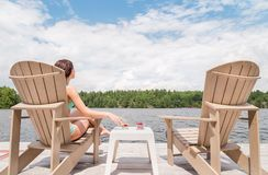 Young woman on a Muskoka chair with a glass of champagne. stock image