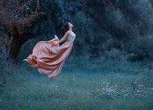 A young woman, a mysterious witch is floating in the air like a butterfly. A luxurious, long dress flutters in the wind stock photo