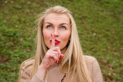 Young woman mysteriously urges to be quiet Stock Photography