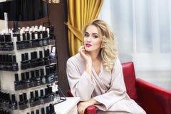 Young woman in nail salon choosing nail polish color to apply Royalty Free Stock Image