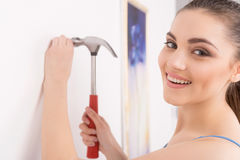 Young Woman Nailing Into New Wall. Beautiful brunette holding hammer and smiling Stock Photo