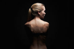 Young woman with naked back.sport body girl. Young woman with naked back over black background.sport body girl Royalty Free Stock Images