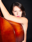 Young woman naked by double bass Stock Images