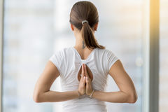 Young woman in Namaste behind the back against floor window. Young woman practicing yoga, making Namaste behind the back, working out, wearing sportswear, white stock image