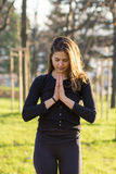 Young woman in Namaste position in park. Woman with folded hands in yoga Namaste position or in prayer in outdoor park Stock Photo
