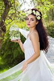 Young woman with natural flowers in hair and birdcage Royalty Free Stock Photography
