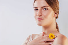 Young woman with natural makeup and smooth skin holding a flower. Organic cosmetics concept Royalty Free Stock Image