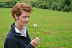 Young woman in the nature. She stays in a meadow Stock Photo