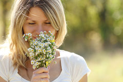 Young woman on nature. With a bouquet of flowers Royalty Free Stock Photography