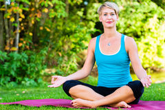 Young woman in nature doing yoga Royalty Free Stock Photography