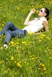 Young woman in nature smelling a flower Stock Image