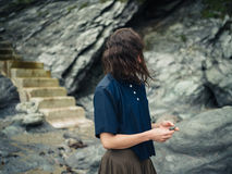 Young woman in nature by stairs leading up cliff Stock Photo