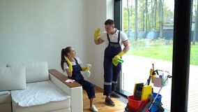 Young woman nd man from cleaning service dressed in workwear and rubber gloves dancing in house