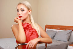 A young woman near bed. A young woman sitting near bed Royalty Free Stock Photography