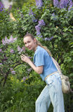 Young woman near  blossoming lilac Stock Photo
