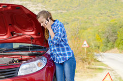 Young woman near broken car speaking by phone Royalty Free Stock Photos
