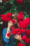 Young woman near the bush of red roses in a garden stock photos