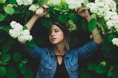 Young woman near bush of white flowers in a garden royalty free stock image