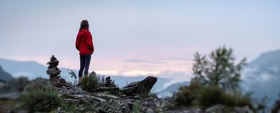 Young woman near cairns. Panorama with lady hiker standing on top of the mountain among stacked stones and enjoying sunset over the valley. Altai, Russia royalty free stock images