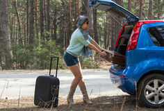 Young woman near the car with a suitcase on the road Stock Photo