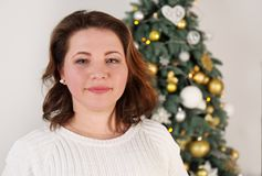Young woman near a Christmas tree. Portrait of a young woman near a Christmas tree Royalty Free Stock Image