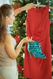 Young woman near Christmas tree selecting Christmas outfit stock photography