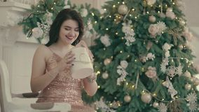 Young woman near the Christmas tree and unpacks presents. Young attractive woman sits on a sofa near the Christmas tree and unpacks presents stock video