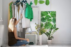 Woman near clothes rack indoors. Stylish dressing room interior. Young woman near clothes rack indoors. Stylish dressing room interior royalty free stock image