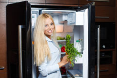 A young woman near the fridge with healthy food. Royalty Free Stock Photography