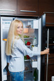 A young woman near the fridge with healthy food. Royalty Free Stock Images