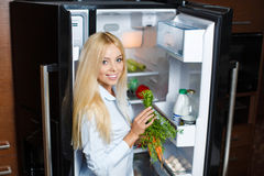 A young woman near the fridge with healthy food. Stock Image
