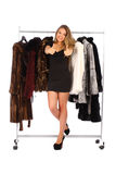Young woman near the hanger with a fur coats Royalty Free Stock Photos