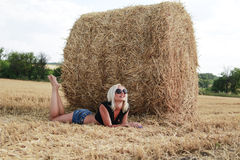 Young woman near haystacks. Beautiful young woman outdoors near haystacks Stock Photos
