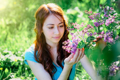 Young woman near the lilac bush in the spring park Royalty Free Stock Images