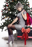 Young woman near new year tree makes shopping Royalty Free Stock Image