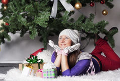 Young woman near new year tree with present Stock Photos