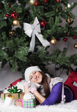 Young woman near new year tree with present Stock Photo