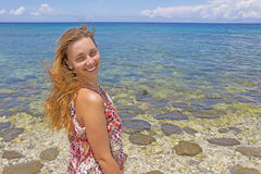 Young woman near sea. Loose red hair and smile on her face. Sea view with pretty girl portrait. Royalty Free Stock Images