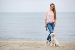 A young woman near the sea with a puppy Retriever Royalty Free Stock Image