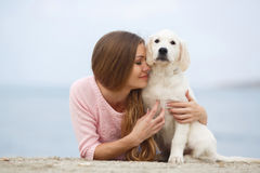 A young woman near the sea with a puppy Retriever Royalty Free Stock Photography