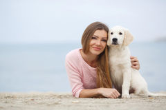 A young woman near the sea with a puppy Retriever Stock Images