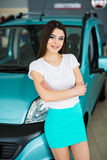 Young woman near their new bought car at the car dealership Royalty Free Stock Photography
