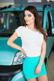 Young woman near their new bought car at the car dealership Royalty Free Stock Photos