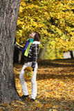 Young woman near the tree. Young woman stays near large tree with maple leafs in hand in the autumn forest Royalty Free Stock Image