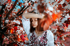 Young  woman near the tree with red leaves. Beautiful young brunette woman standing near the tree with red leaves on a warm summer day Stock Image