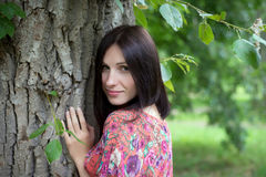 A young woman near the tree in the summer. Young woman in red dress with flowers is standing near tree and looking at the camera in the summer Royalty Free Stock Image