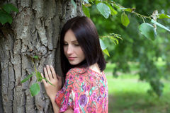A young woman near the tree in the summer. Young woman in red dress with flowers standing near the tree and looks down in the summer Stock Images