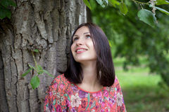 A young woman near the tree in the summer. Young woman in red dress with flowers standing near the tree, smiling and looking up in the summer Stock Photography